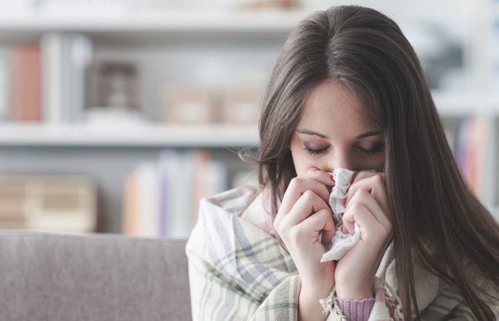 A woman with a blanket around her shoulders blowing her nose with a tissue.