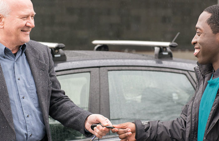 A smiling patient giving his car keys to a welcoming Impark HEALTH valet attendant.