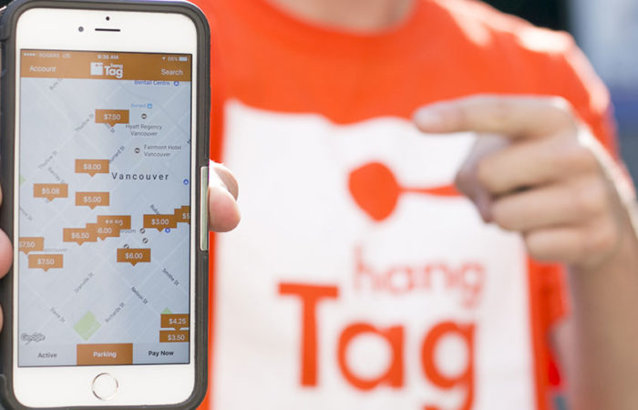 A man wearing a hangTag shirt points to a smartphone depicting hangTag's interactive map.