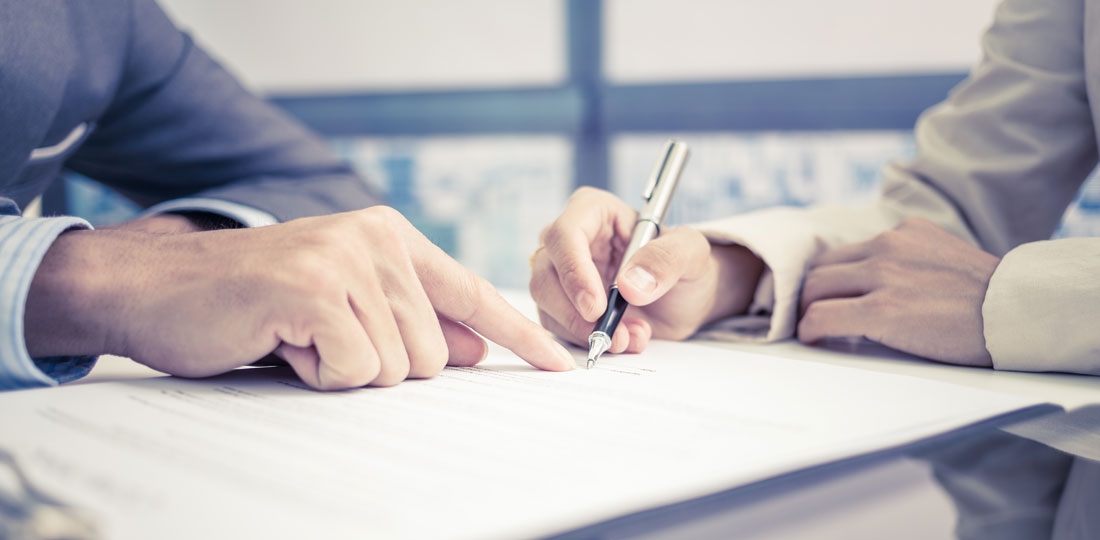 A consultant showing a businessman where his signature is required on a contract.