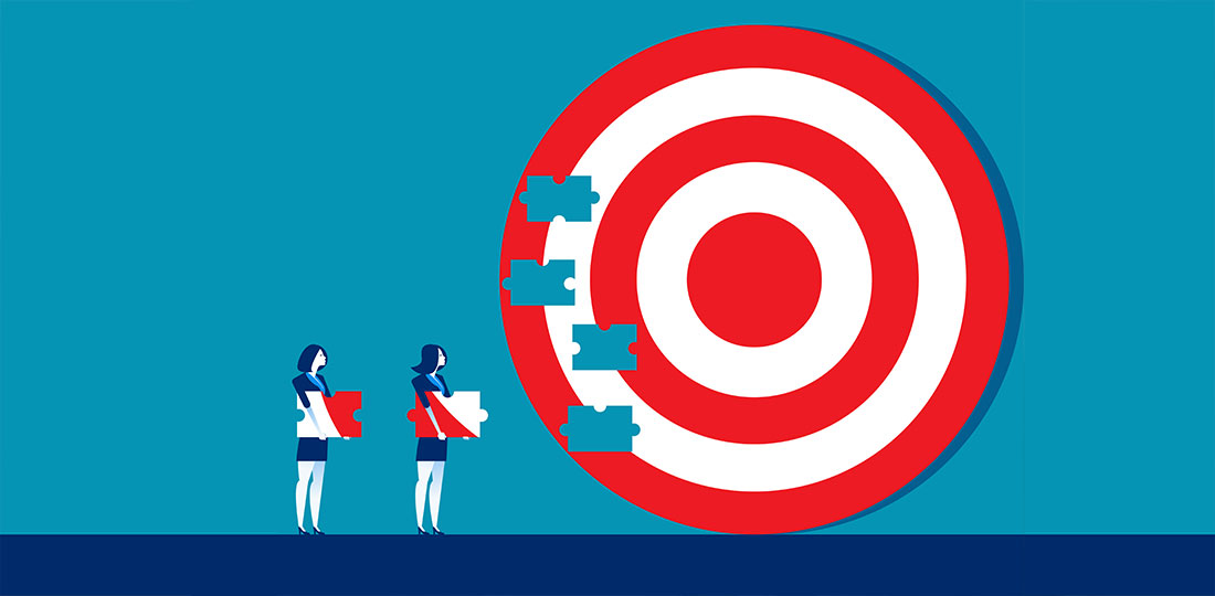 Two businesswomen carrying puzzle pieces towards a large jigsaw of a bullseye target. Illustration.