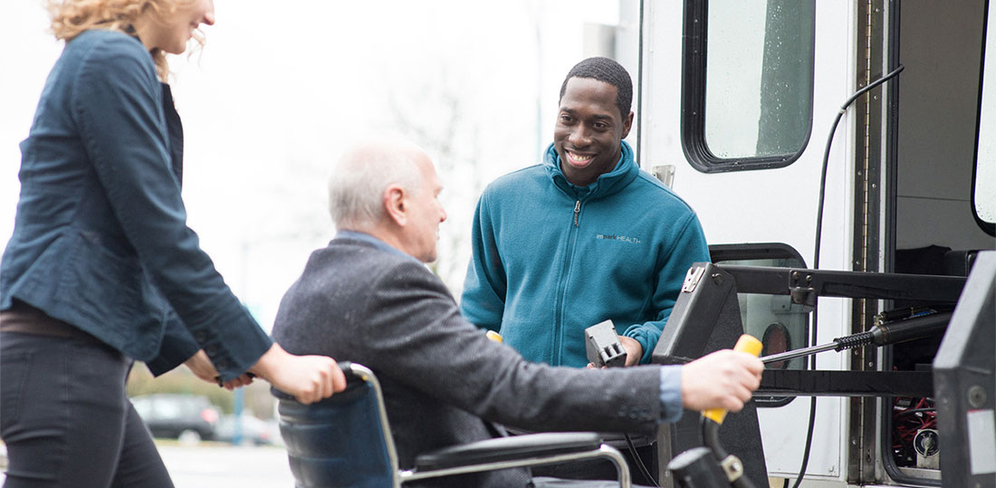 A smiling Impark HEALTH attendant assisting a man in a wheelchair who is boarding an Impark HEALTH shuttle bus.