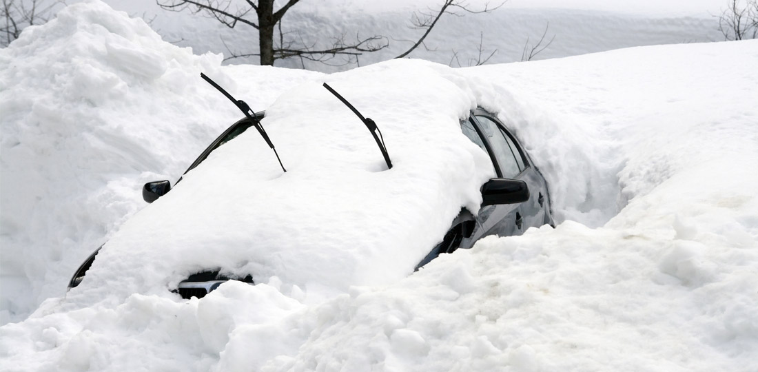 A parked car is barely visible under a mound of snow.